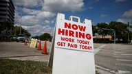 "A ""Now Hiring"" sign advertising jobs at a hand car wash is seen along a street, as the spread of the coronavirus disease (COVID…"