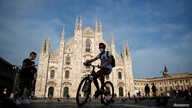 FILE PHOTO: A man wearing a protective face mask rides a bicycle at Piazza Duomo, as Italy eases some of the lockdown measures…