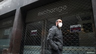 A man wearing a face mask as a protective measure against the coronavirus disease (COVID-19) walks past a closed currency…