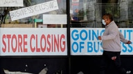 FILE - In this May 21, 2020 file photo, a man looks at signs of a closed store due to COVID-19 in Niles, Ill.  The U.S…