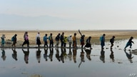 School children walk to take part in a lesson in an open-air classroom in Qarghayi district of Laghman Province on January 20,…