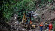 Rescuers stand at the site where seven people went missing after a mudslide caused by constant rains, in Santo Tomas, El…