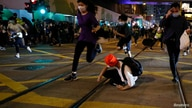 Pro-democracy demonstrators run away as riot police disperse them with pepper-spray pellet during a protest to mark first…