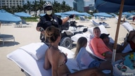 A police offices talks to beachgoers as beaches are reopened with restrictions to limit the spread of the coronavirus disease …