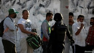 """An state police officer talks with migrants near the migrant shelter """"Casa INDI"""", where some migrants have been infected by the…"""