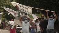 People raise white flags begging for food from drivers on the Golden Highway in Ilopango, El Salvador, Tuesday, May 19, 2020…