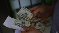 A woman counts money outside a U.S. remittance collection agency in San Isidro, 70 km northeast of San Salvador, on June 10,…