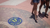 Beachgoers walk past a social distancing sign on the floor as beaches are reopened with restrictions to limit the spread of the…