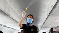 A flight attendant wearing a face mask sprays disinfectant inside a plane at Sharm el-Sheikh International Airport, following…