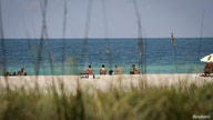FILE PHOTO: Beachgoers sunbathe as beaches are reopened with restrictions to limit the spread of the coronavirus disease (COVID…
