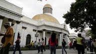 People walk past the National Assembly building during a parliamentary session in Caracas, Venezuela December 14, 2016. REUTERS…