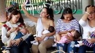A mother takes a selfie as she nurses her child to mark the World Breastfeeding Week to promote global support for…