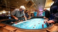 Gene Koonce of Drake, Colorado plays on a craps table fitted with protective plexiglass panels during the reopening of Bellagio…