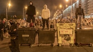 Demonstrators stand on trash containers used as a makeshift barricade during a rally following the presidential election in…