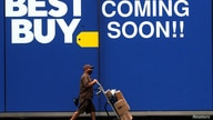 A delivery person passes by a sign for a new Best Buy store in New York City, U.S., August 12, 2020. REUTERS/Brendan McDermid