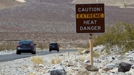 FILE PHOTO: A sign warns of extreme heat as tourists enter Death Valley National Park in California June 29, 2013. REUTERS…