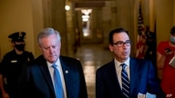Treasury Secretary Steven Mnuchin, right, accompanied by White House chief of staff Mark Meadows, left, speaks to members of…
