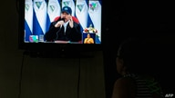 A woman watches a TV broadcast of Nicaraguan President Daniel Ortega speech during the 41st anniversary of the Sandinista…