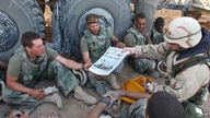 In this image released by the US Navy 07 April, 2003, Command Sgt Maj John Sparks, delivers copies of Stars and Stripes 04…