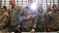 A United States Airman holds up an American Flag as U.S. President Donald Trump delivers remarks to military personnel in an…