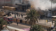 Iraqi firemen extinguish a blaze at the gates of the U.S. embassy compound in Baghdad, Iraq January 1, 2020.  DoD/Lt. Col…