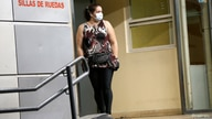 A woman wearing a face mask leaves Hospital Cosme Argerich, after the first fatality from coronavirus in Latin America was…