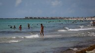 A woman walks along the shallows as beaches are reopened with restrictions to limit the spread of the coronavirus disease …