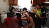 Los Angeles Unified School District (LAUSD) students Keiley Flores, 13, Andrea Ramos, 10, Alexander Ramos, 8, work on school…