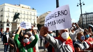 People hold placards during a protest against government as Spanish Prime Minister Pedro Sanchez meets Madrid Regional leader…