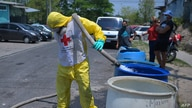 A member of the Red Cross fills tanks with water for residents of the colony Los Almendros, in Ciudad Delgado, El Salvador, as…
