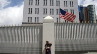 An indigenous Bolivian woman stands in front of the U.S. embassy as she looks at demonstrators during a protest in La Paz…