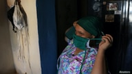 Nurse Vanessa Castro removes her face mask as she reaches home after a night shift in Central Hospital in Maracay, amid the…
