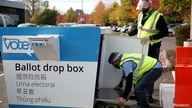 John Machowski and Matthew Roggenkamp open a drop box to collect ballots outside the King County Elections headquarters in…