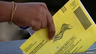 FILE PHOTO: An election worker places mail-in ballots into a voting box at a drive-through drop off location at the Registrar…