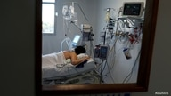 FILE - A patient suffering from the coronavirus disease (COVID-19) is seen in an intensive care unit of a hospital, on the outskirts of Buenos Aires, Argentina, Oct. 16, 2020.