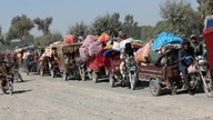 FILE - Afghan families leave their houses after fighting between the Afghan military and Taliban insurgents in Helmand province, southern Afghanistan, Oct. 13, 2020.