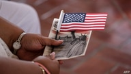 A woman holds a US flag before she became US citizen during a special naturalization ceremony in honor of Citizenship Day and…