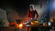 A woman playing the role of Bridget Fuller scrapes cinnamon into a bowl to make pancakes in a home at Plimoth Plantation in…