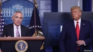 U.S. President Donald Trump listens as Dr. Scott Atlas speaks to reporters during a news conference in the Brady Press Briefing…