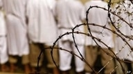 FILE - Detainees stand during an early morning Islamic prayer at the US military prison in Guantanamo Bay, Cuba, in 2009.