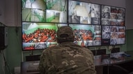 FILE - A fighter with the Syrian Democratic Forces (SDF) monitors on surveillance screens prisoners accused of being affiliated with the Islamic State (IS) group, at a prison in the northeastern Syrian city of Hasakeh, Oct. 26, 2019.