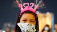 "A girl wearing a mask and ""2021"" head band looks on at a shopping mall as The New Year countdown celebrations and crowded…"