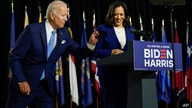Democratic presidential candidate former Vice President Joe Biden retrieves his face mask from the podium as his running mate…