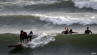 Surfers enjoy the raising temperatures at a beach in Lima, on October 22, 2020, amid the new coronavirus pandemic. - Peruvians…