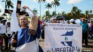 A demonstrator holds an image of Jesus Christ, as she protest against Nicaraguan President Daniel Ortega's government during a…