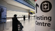 A sign pointing to a testing centre is seen, as tighter rules for international travellers start, at Heathrow Airport, amid the…
