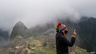 A tourist poses for a selfie in front of the archaeological site of Machu Picchu, in Cusco, Peru on November 02, 2020, amid the…