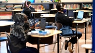(FILES) In this file photo taken on November 16, 2020 Students sit with their laptop computers at St. Joseph Catholic School in…
