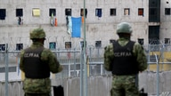 Soldiers stand guard outside the CRS Turi prison in Cuenca, Ecuador on February 24, 2021. - At least 79 inmates died in…
