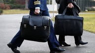 """A military aide carries the so-called """"nuclear football,"""" which contains launch codes for the U.S. nuclear arsenal and which…"""